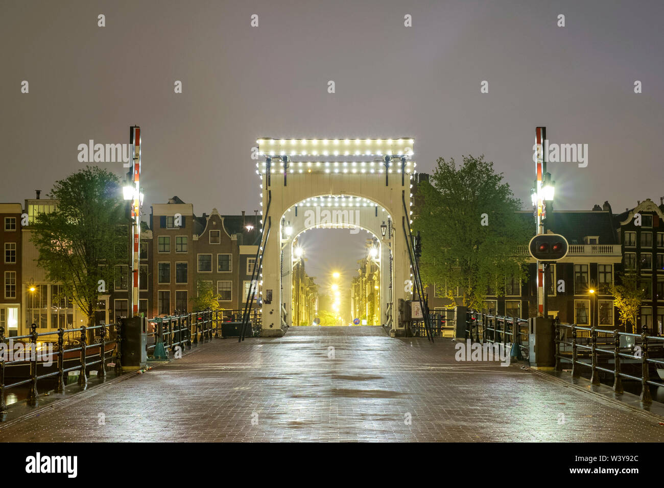 Magere Brug illuminated at night on foggy evening, Amsterdam, North Holland, Netherlands - Stock Image