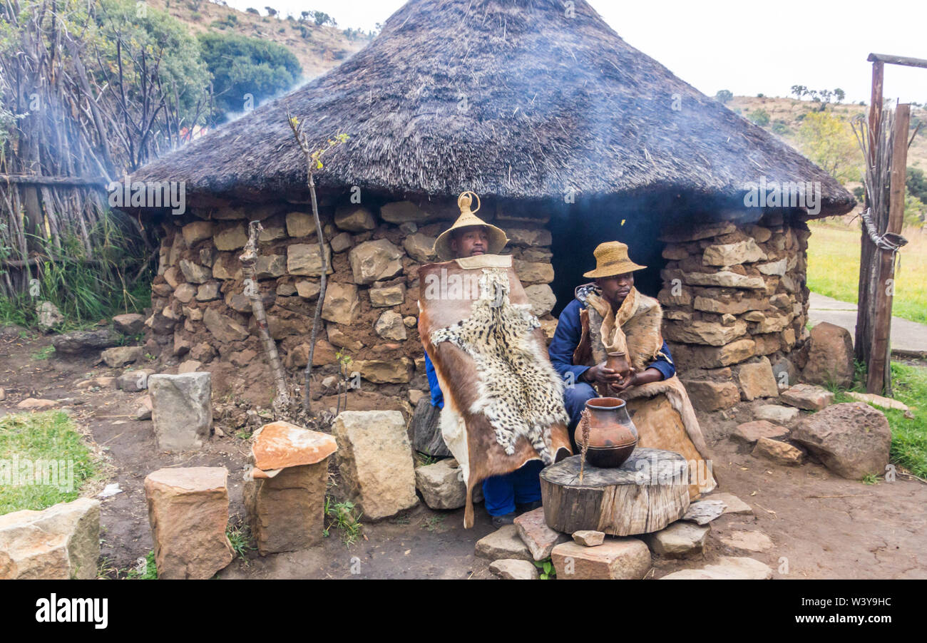 Basotho cultural village rural scene with two black African men dressed in traditional animal skins or hides outside a stone thatch rondawel or hut Stock Photo