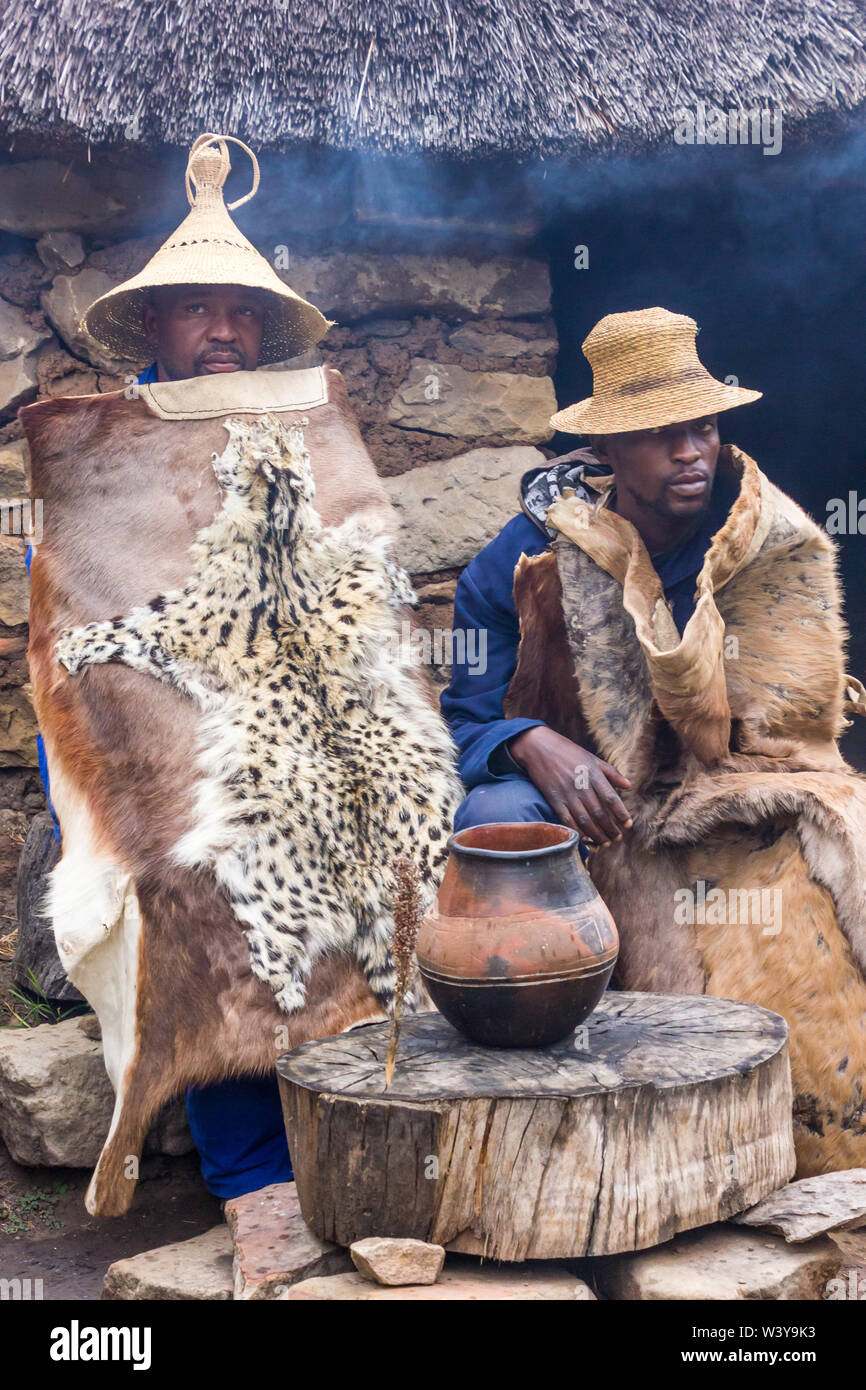 two Basotho black African men sitting in traditional animal skins or hides outside a stone thatch rondawel or hut with a clay pot filled with beer Stock Photo