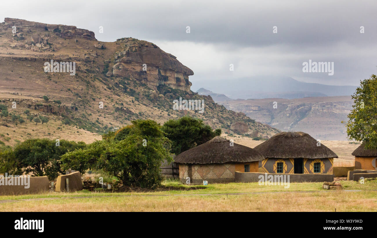 Basotho cultural village traditional thatch round or circular rondawel huts against a mountain in rural national park of Free State in South Africa Stock Photo