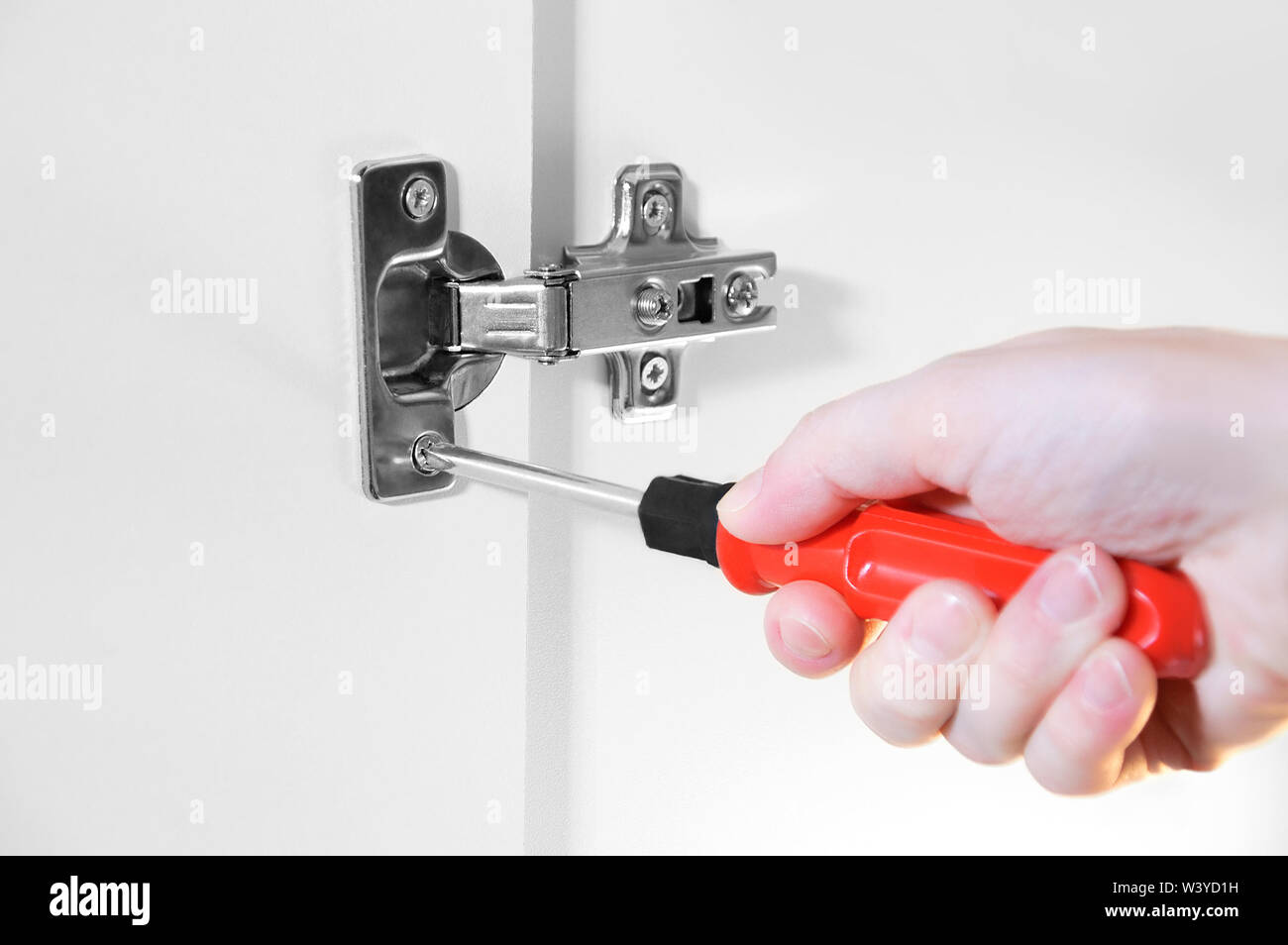 Home repair. The girl fastens with a screwdriver a metal hinge on the cabinet door. - Stock Image