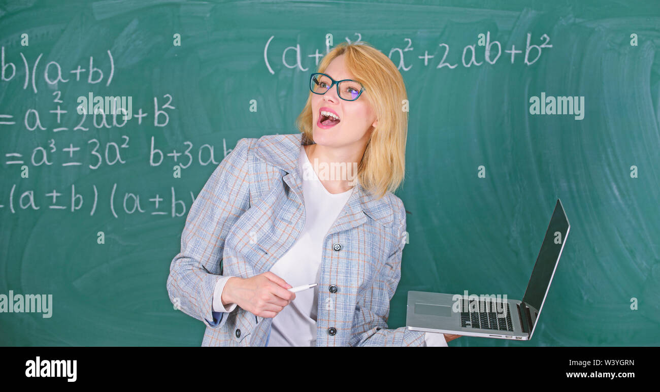 Educator smart clever lady with modern laptop searching information chalkboard background. Learn it easy way. Woman teacher wear eyeglasses holds laptop surfing internet. Digital technologies concept. - Stock Image