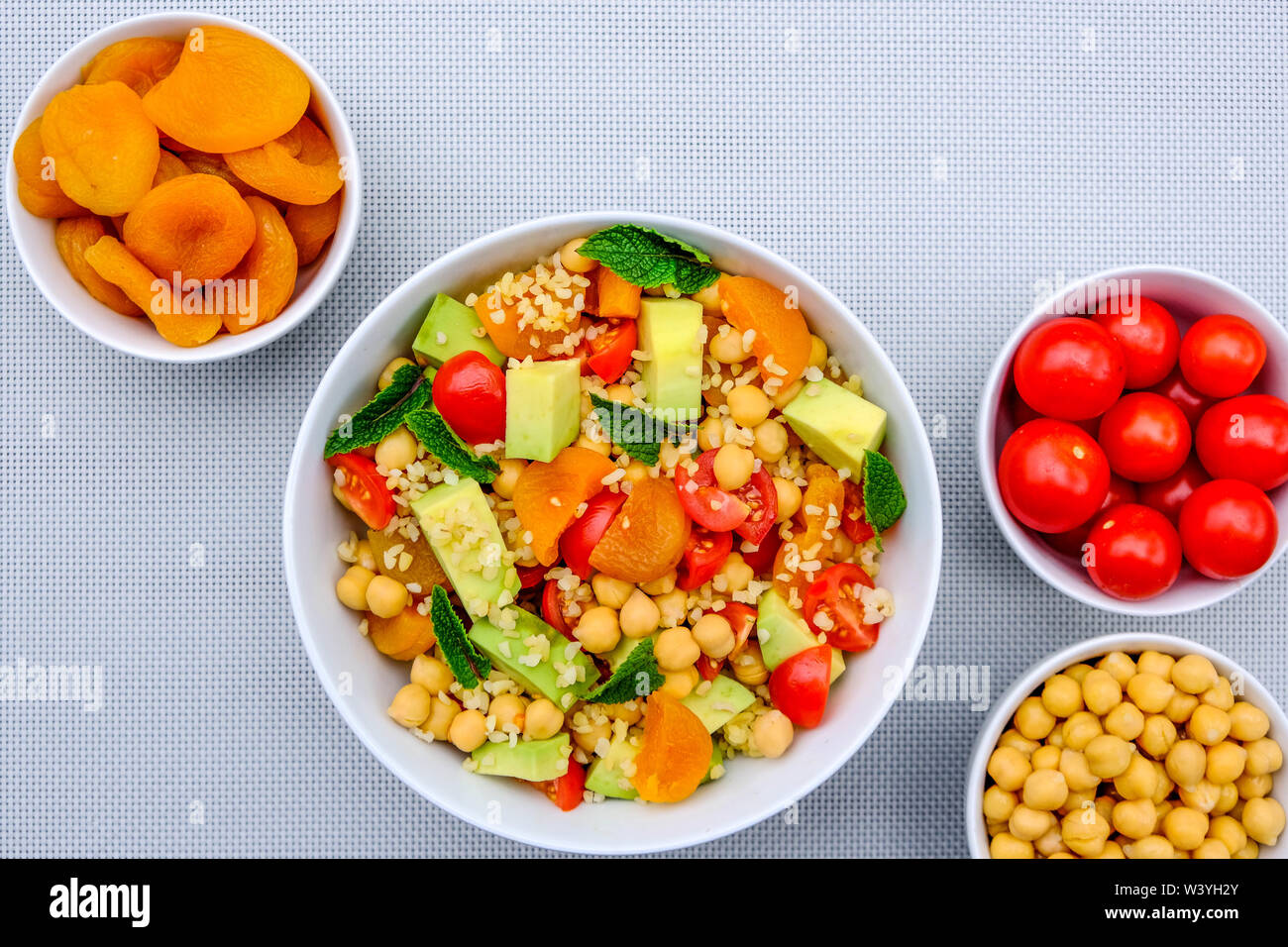 Healthy Vegetarian Lunch Bowl With Fruit and Vegetables Including Avocado, Apricots, Tomatoes, Chickpeas and Bulgur Wheat - Stock Image