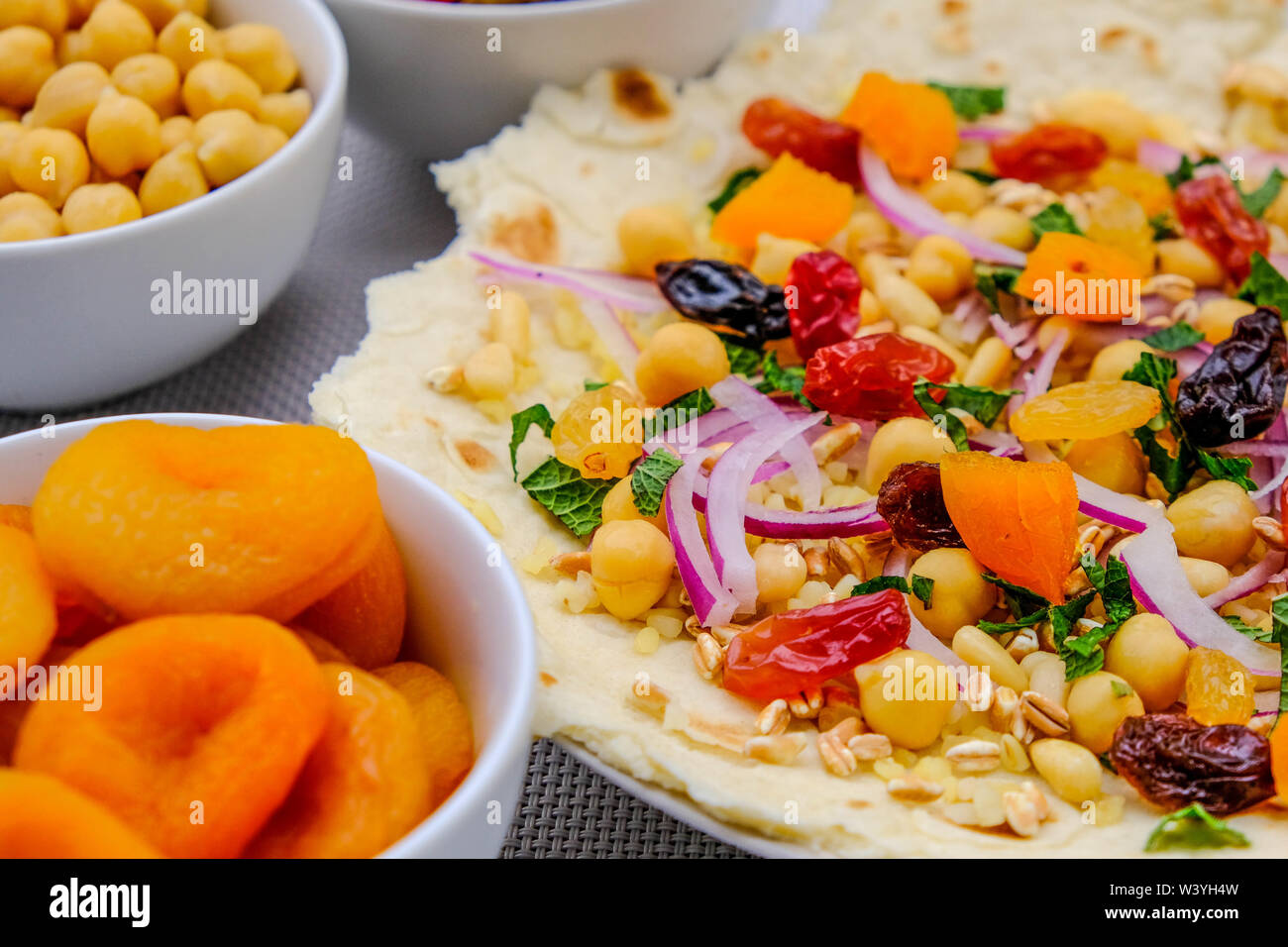 Healthy Pizza Base With Fruit and Nuts, apricots, sultanas, Raisins, Pine Nuts, red Onion and Chickpeas - Stock Image
