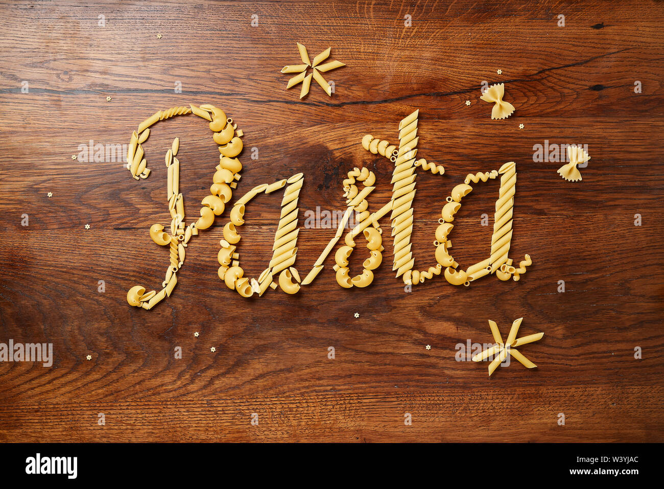 Food lettering. Concept. Various pasta on wooden table. Cooking concept. Top view. - Stock Image
