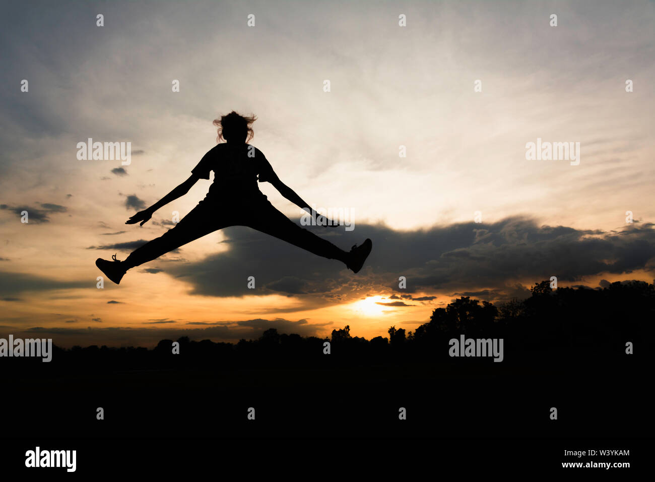 Silhouette of cheerful positive and full energy girl jumping in the air for life energy concept. - Stock Image