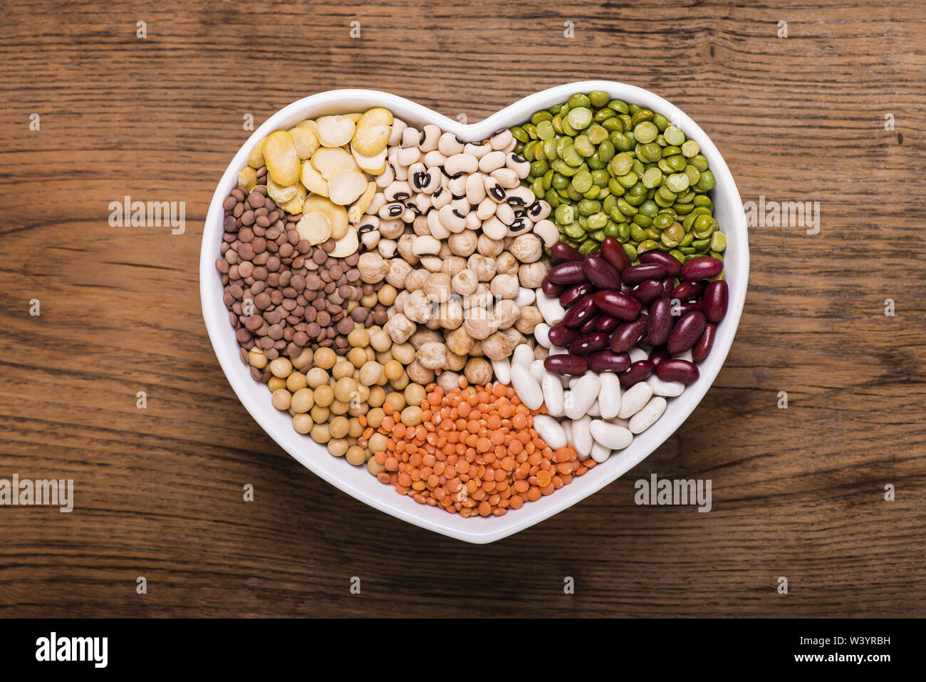 ceramic bowl in the shape of a heart full of different types of dry legumes - Stock Image