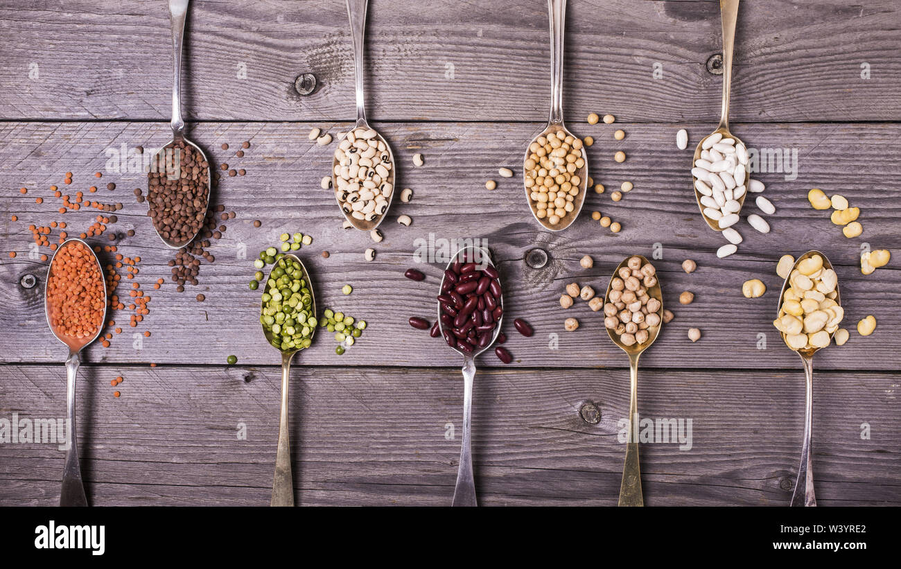 composition of dry legumes of different types, color and flavor on rustic wood background - Stock Image