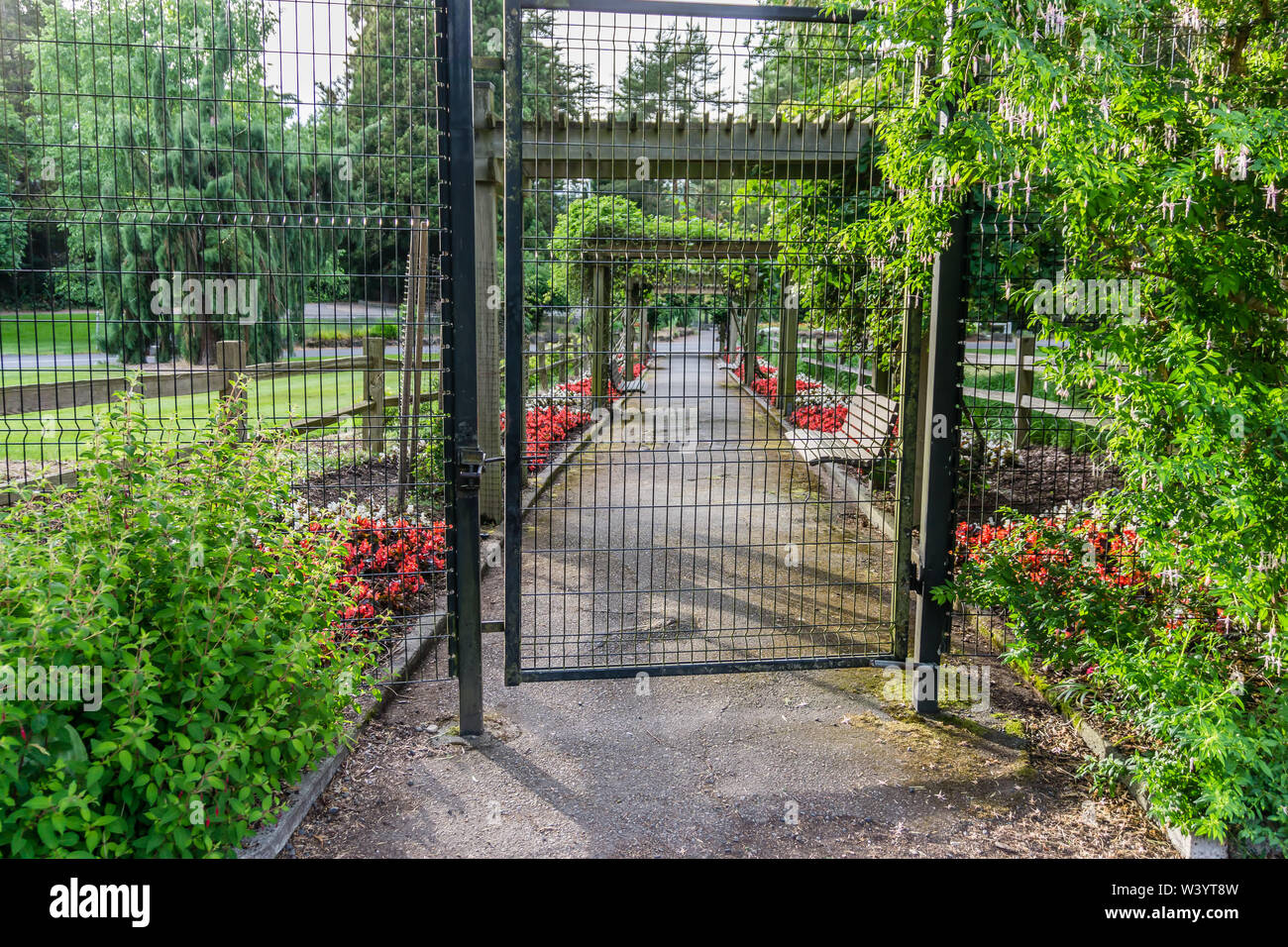 A view of a gate and walkway at the rose garden in Point Defiance Park in Tacoma, Washington. - Stock Image