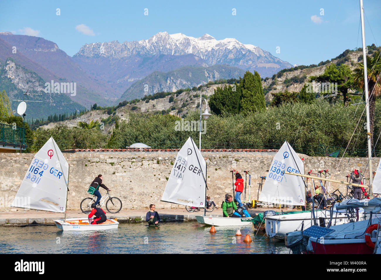 Optimist sailing boats, motorboat, tourists at small harbor Porticciolo, Lago di Garda, Lake Garda in Torbole - Nago, Riva, Trentino , Italy at April - Stock Image