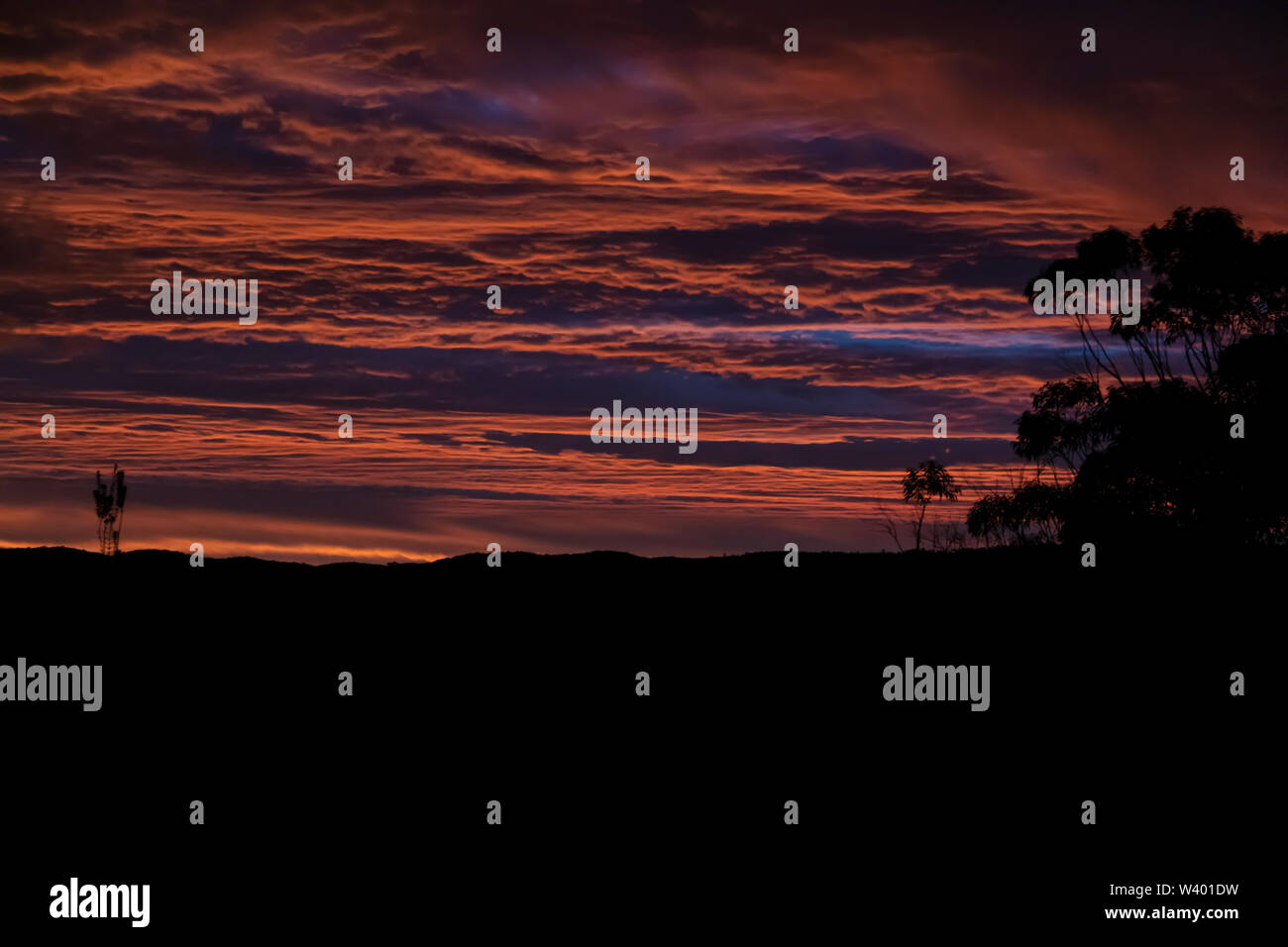 Vibrant red sunset and clouds across a Gully. - Stock Image