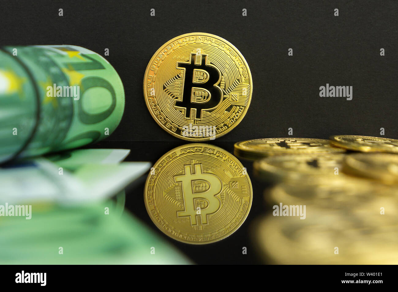 Euro vs bitcoin cryptocurrency. There are one hundred euro banknotes and big golden btc coins on a black background. Golden bitcoin over Euro money. - Stock Image