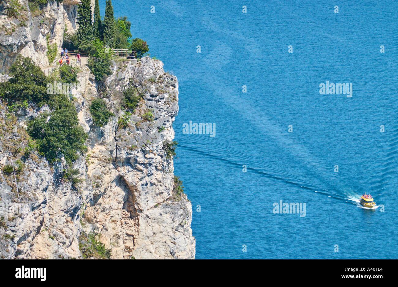Bike road up to Pregasina  and a tourist cruising motorboat at Lago di Garda, Lake Garda in Torbole - Nago, Riva, Trentino , Italy at April 17, 2019. - Stock Image