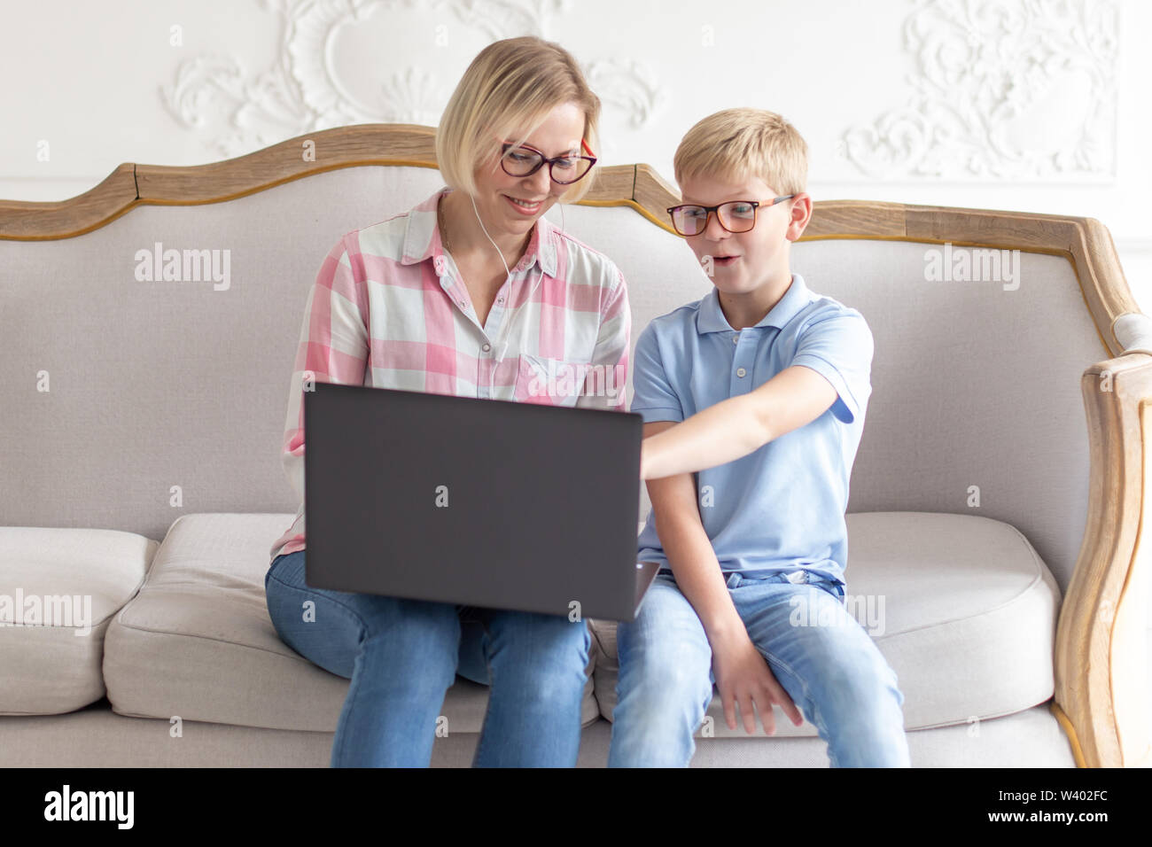 Happy Young Mom And Her Son Sitting On Sofa And Using Laptop