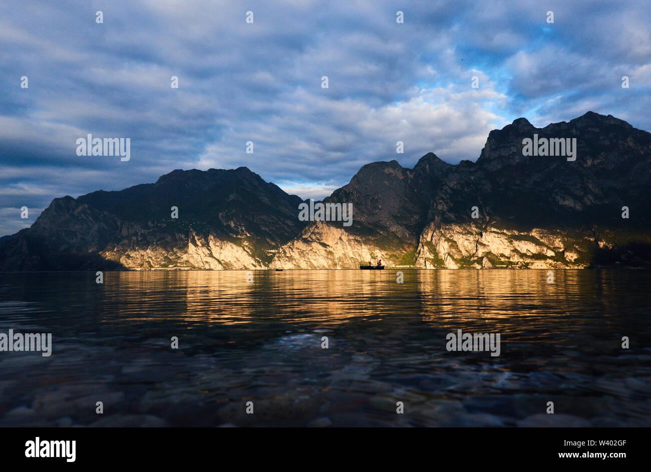 Fisherman fishing at sunrise, Pregasina village, Cima della Nara at Lago di Garda, Lake Garda in Torbole - Nago, Riva, Trentino , Italy at April 15, 2 - Stock Image