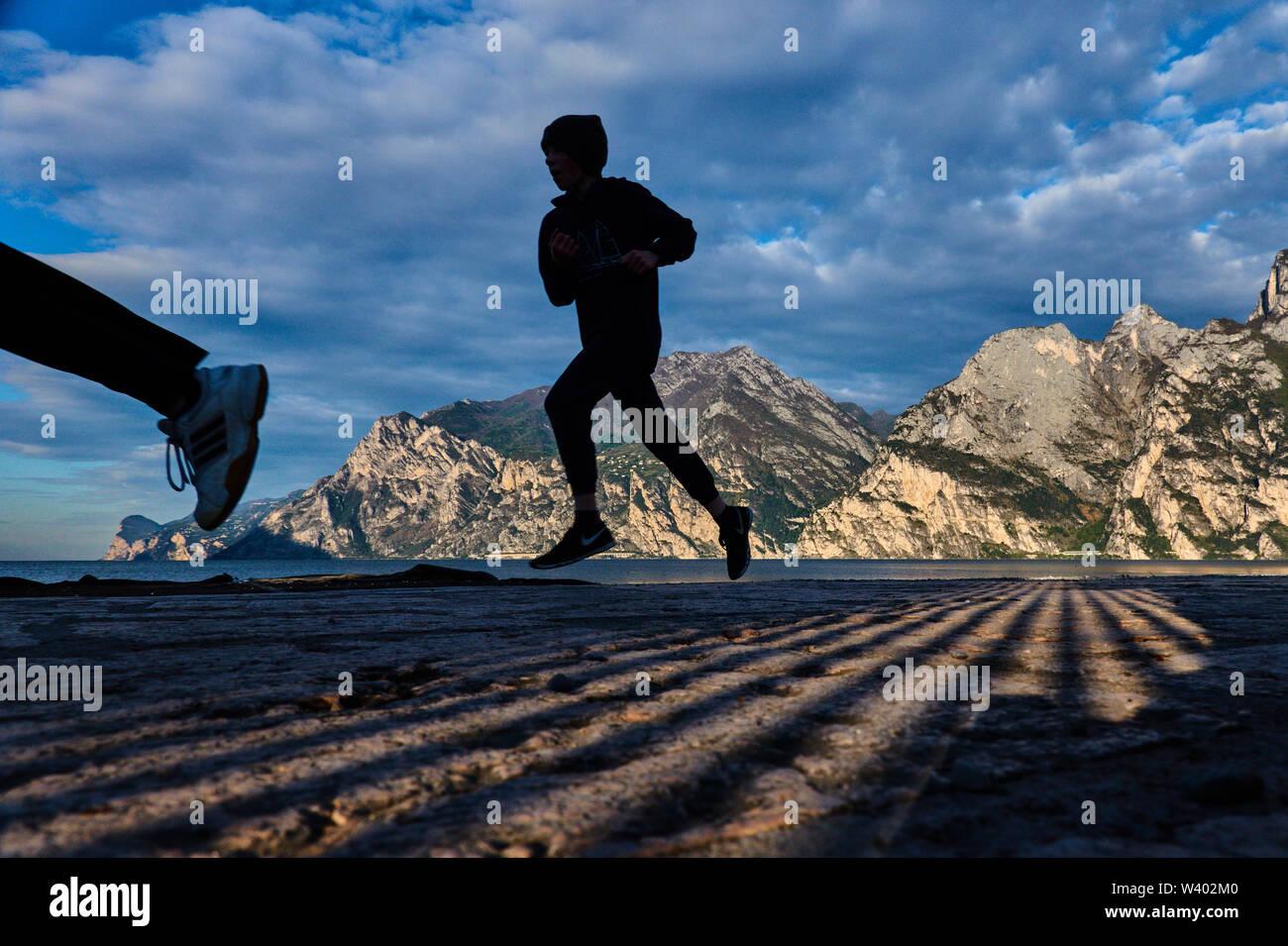 Jogger at north beach on sunrise at Lago di Garda, Lake Garda in Torbole - Nago, Riva, Trentino , Italy at April 15, 2019. © Peter Schatz / Alamy Stoc - Stock Image