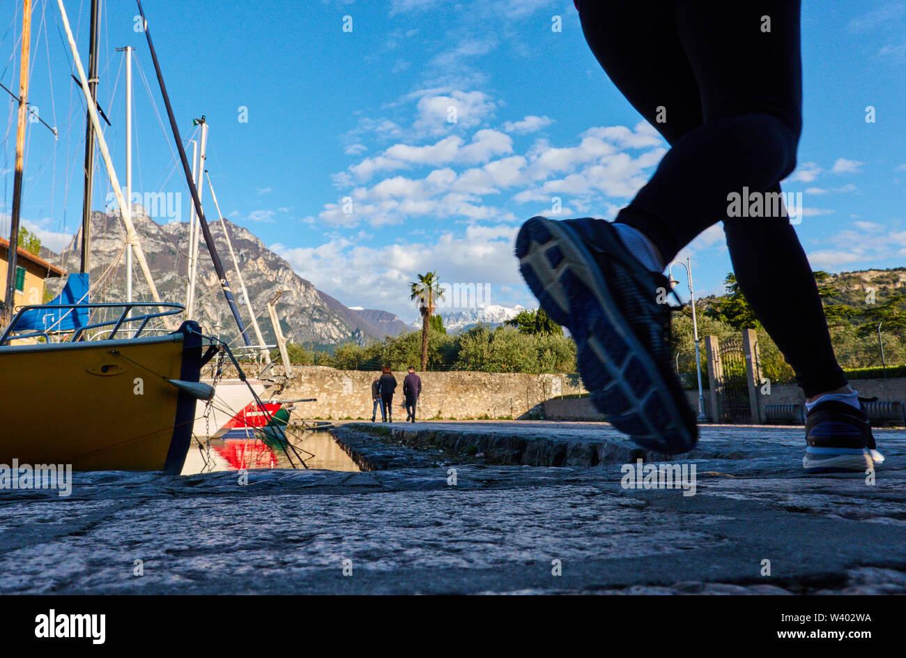 Jogger at north beach on sunrise at small harbor Porticcioloat Lago di Garda, Lake Garda in Torbole - Nago, Riva, Trentino , Italy at April 15, 2019. - Stock Image
