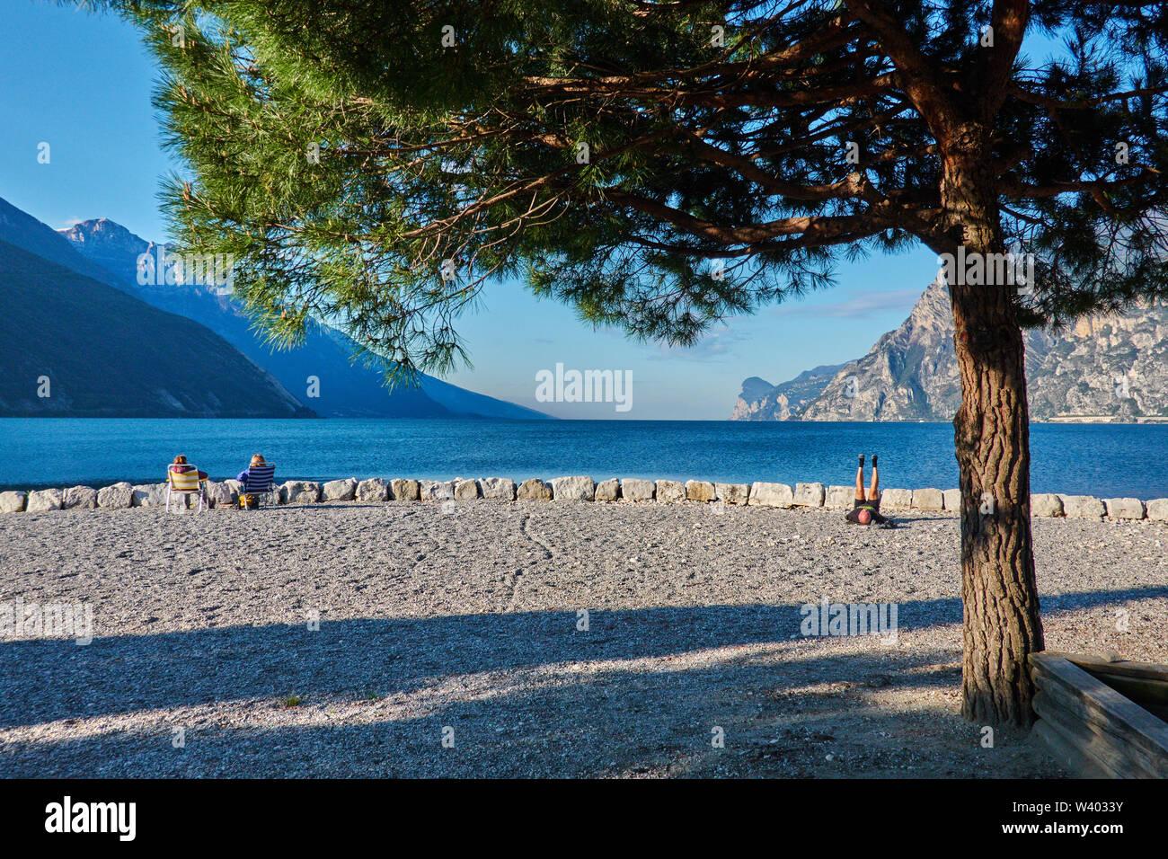 Tourists sitting at the beach at small harbor Porticcioloat Lago di Garda, Lake Garda in Torbole - Nago, Riva, Trentino , Italy at April 15, 2019. © P - Stock Image