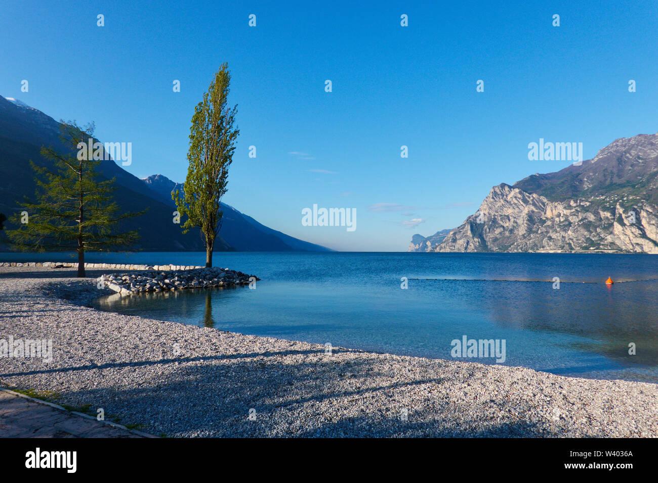 Northern beach on sunrise at small harbor Porticcioloat Lago di Garda, Lake Garda in Torbole - Nago, Riva, Trentino , Italy at April 15, 2019. © Peter - Stock Image