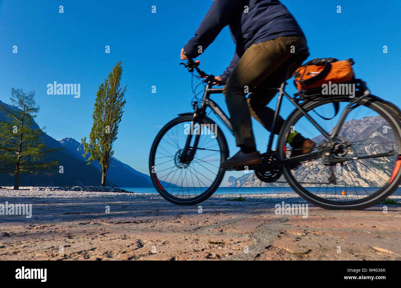 Cyclists at north beach on sunrise at small harbor Porticcioloat Lago di Garda, Lake Garda in Torbole - Nago, Riva, Trentino , Italy at April 15, 2019 - Stock Image