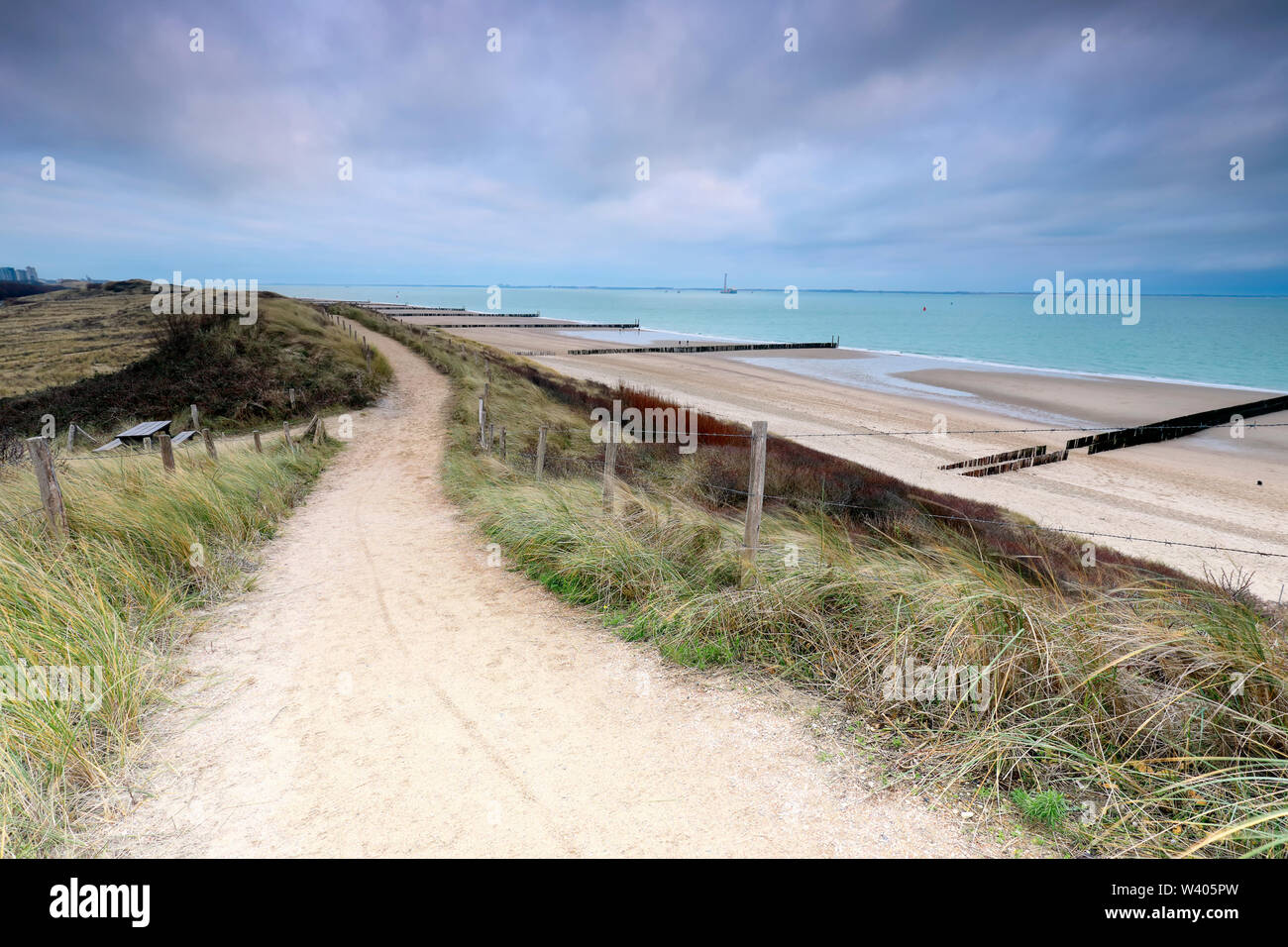path on dune over North sea beach on gloomy day - Stock Image