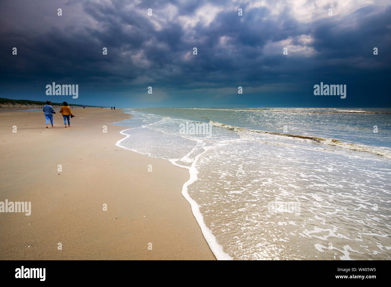 couple walking along the beach in sunshine, Zandvoort, Holland - Stock Image