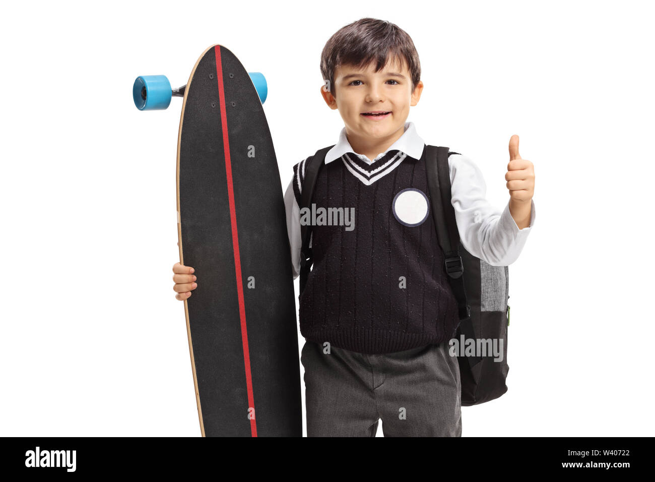 Little schoolboy with a longboard making a thumb up sign isolated on white background - Stock Image