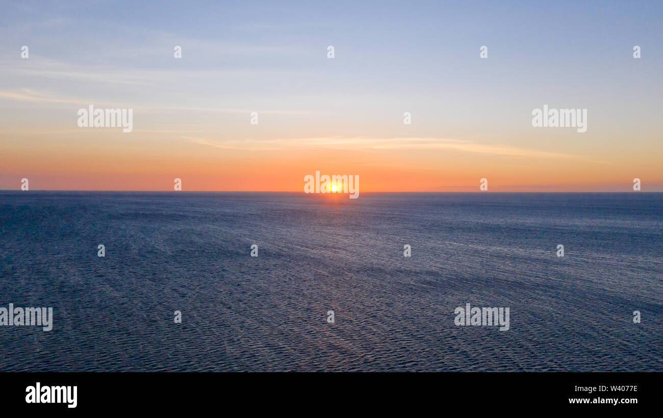 Sunset over the sea in clear weather, view from above. Seascape with evening sun and deep blue sea. - Stock Image