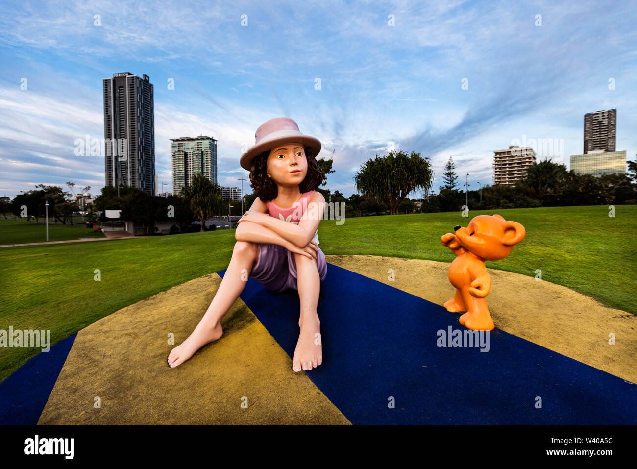 A statue of a young girl, Maddie, and her teddy bear, Mike, sits watch over the Nerang River, Surfers Paradise, Queensland. - Stock Image