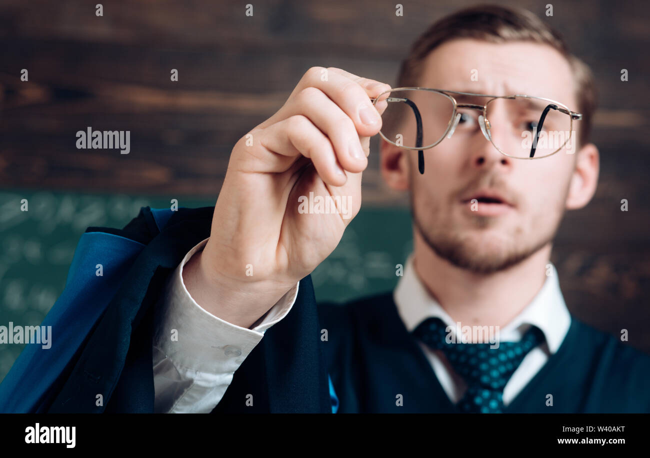 Let me see. Teacher formal wear and glasses looks concentrated, chalkboard background. Chalkboard full of math formulas. Man in end of lesson checking - Stock Image