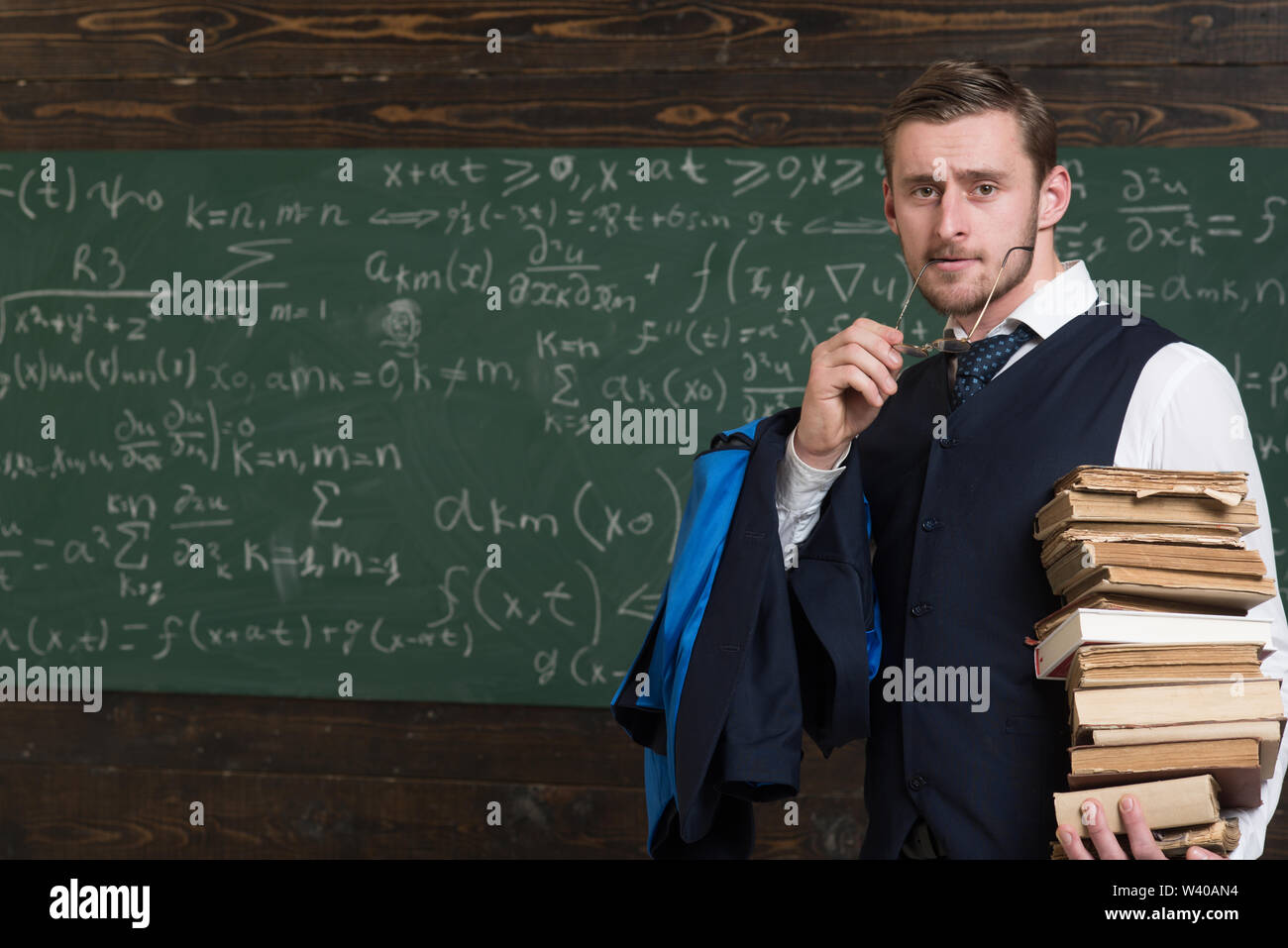 Clear explanation. Teacher formal wear and glasses looks smart, chalkboard background. Chalkboard full of math formulas.Man in end of lesson takes off - Stock Image