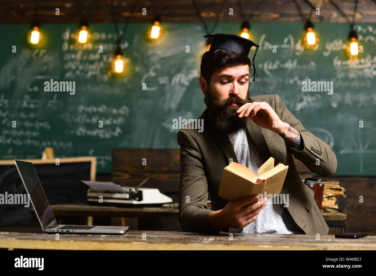 Student studying online courses with computer, Teacher collaborates with colleagues, Happy teacher in classroom, Teachers not only love their subject - Stock Image