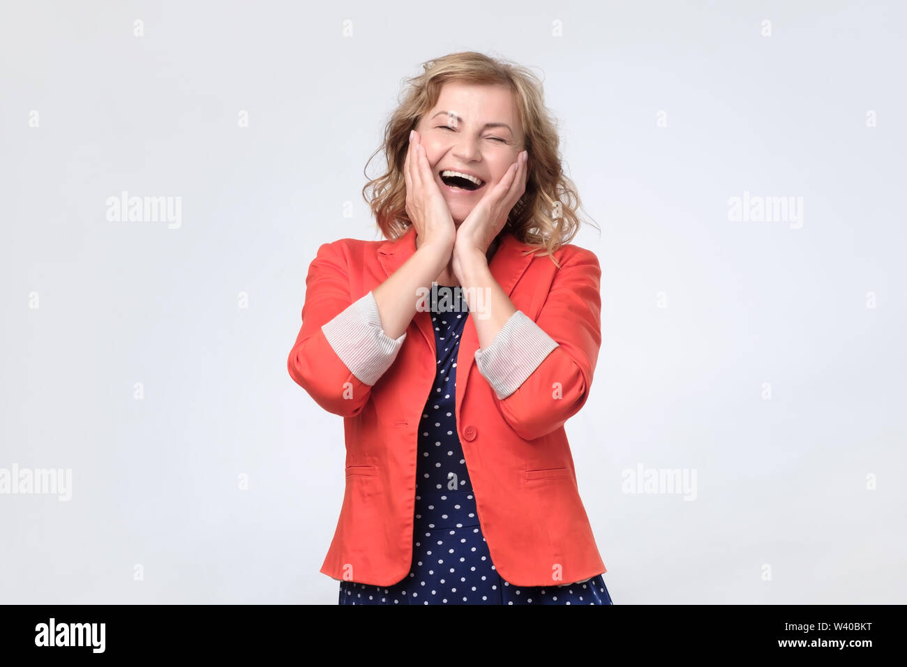 Mature happy woman laughing loudly on joke. - Stock Image