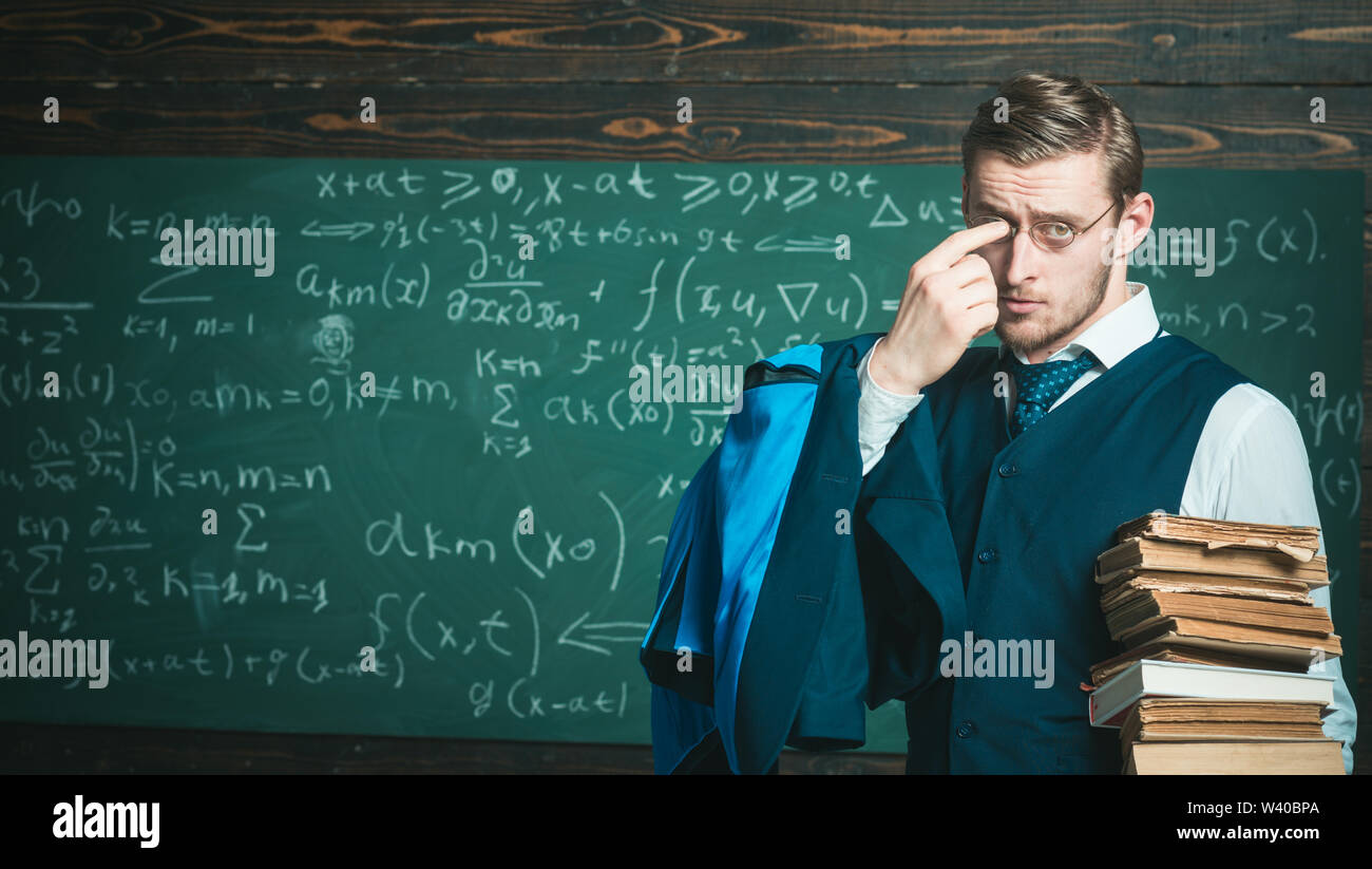 Teacher formal wear and glasses looks smart, chalkboard background. Man in end of lesson takes off eyeglasses. Did you get it Chalkboard full of math - Stock Image