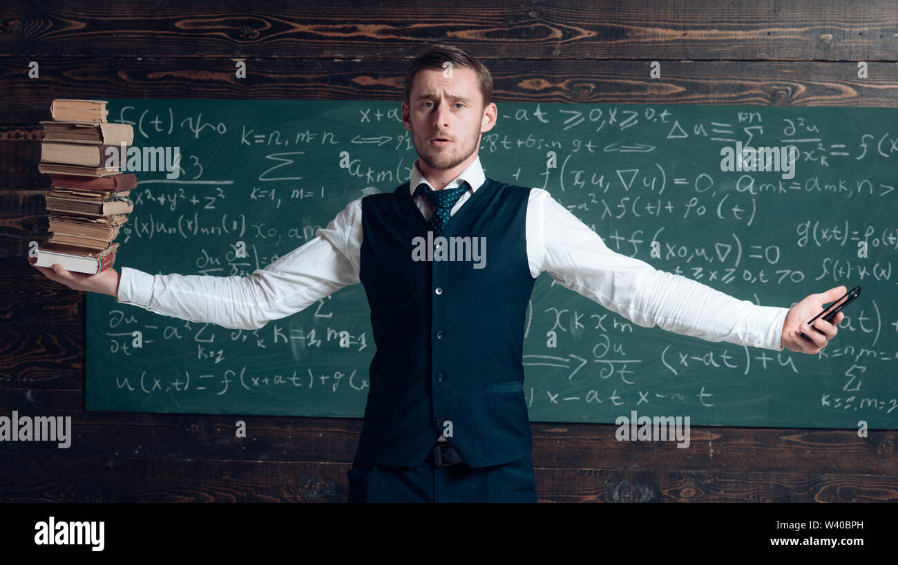 Man teacher balancing in hands pile of books and smartphone as symbol analog and digital information storages. Teacher formal wear, chalkboard backgro - Stock Image