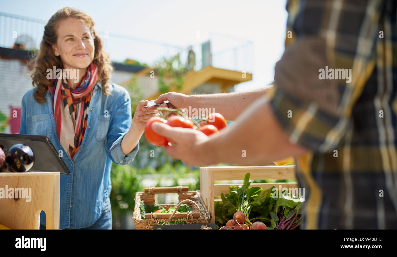 Friendly woman tending an organic vegetable stall at a farmer's market and selling fresh vegetables from the rooftop garden Stock Photo
