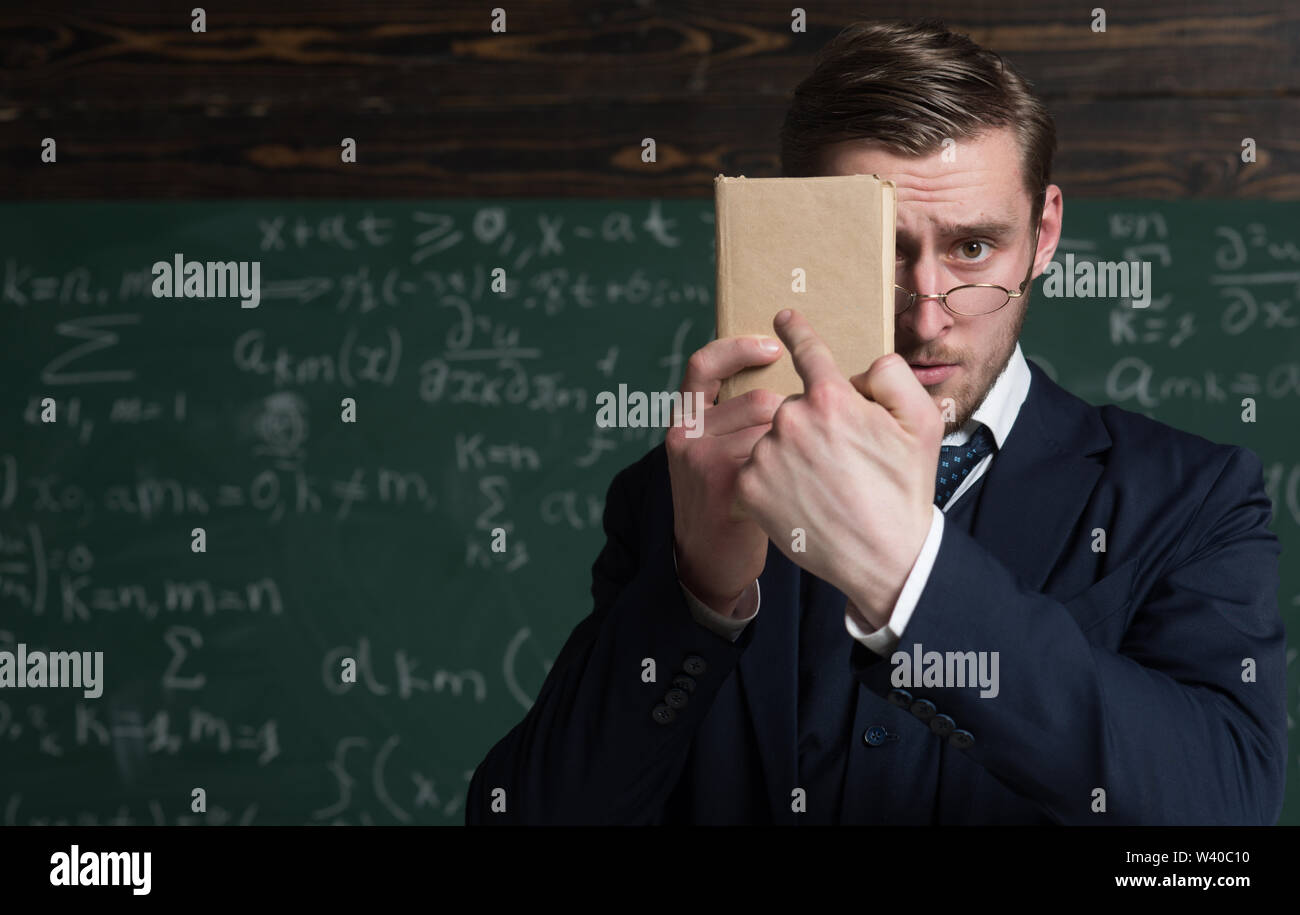You should better learn it. Teacher formal wear and glasses looks smart, chalkboard background. Man unshaven holds book in front of face. Teacher insi - Stock Image