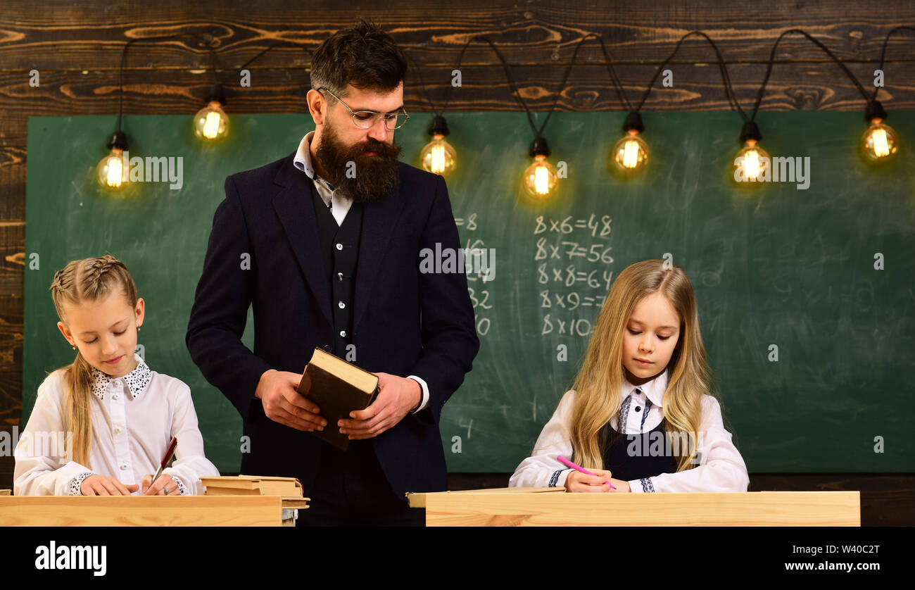 Child needs to stay focused to finish her work. Students build positive relationships with their teachers. Attentive schoolkid is doing his math homew - Stock Image