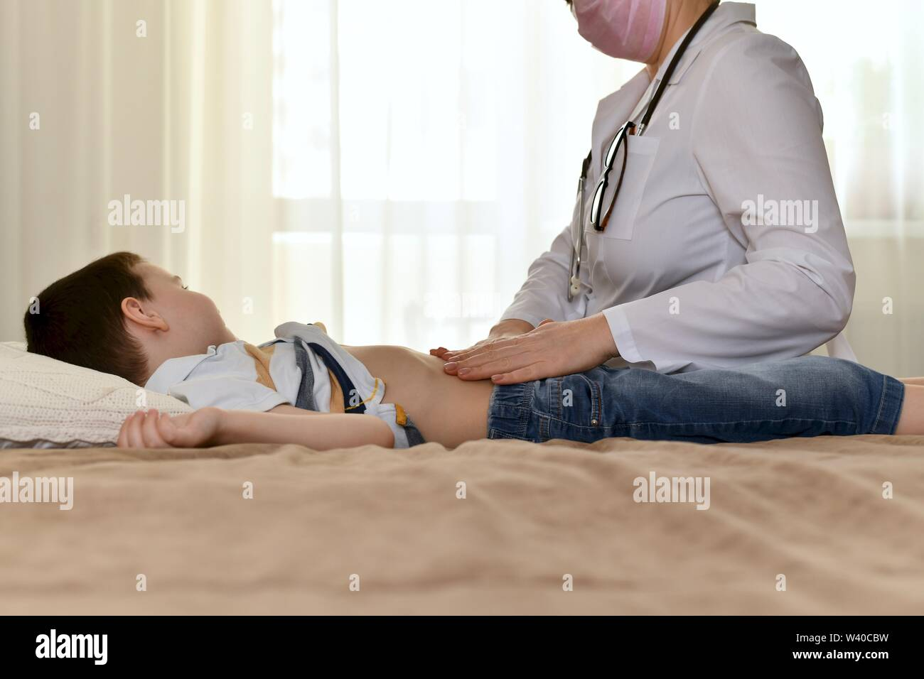 The doctor sits by the bed of the sick child and examines the abdomen. The boy turned his head to the side and calmly watched her actions. Stock Photo