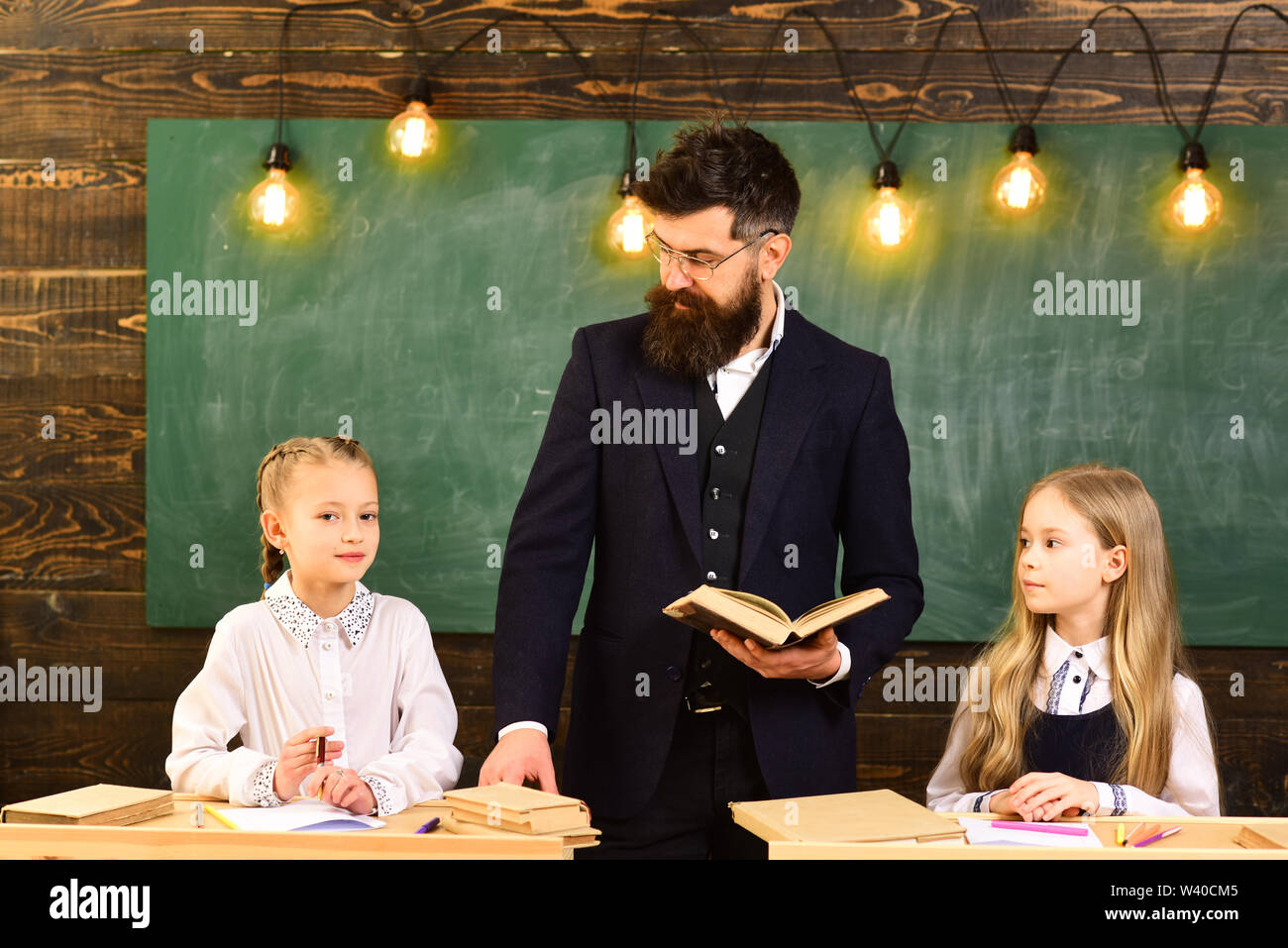 Parents usually put their kids into academic coaching. Attentive students writing something in their note pads while sitting at desks in the classroom - Stock Image