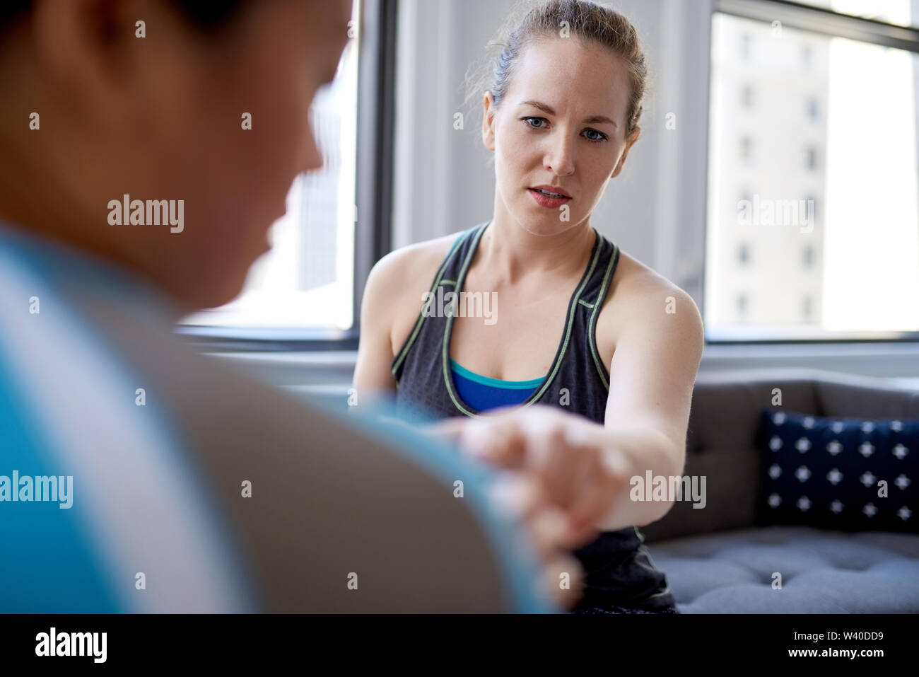Caucasian woman physiotherapist talking to a mid-adult chinese female patient and taking notes on a tablet during a fitness evaluation consultation - Stock Image