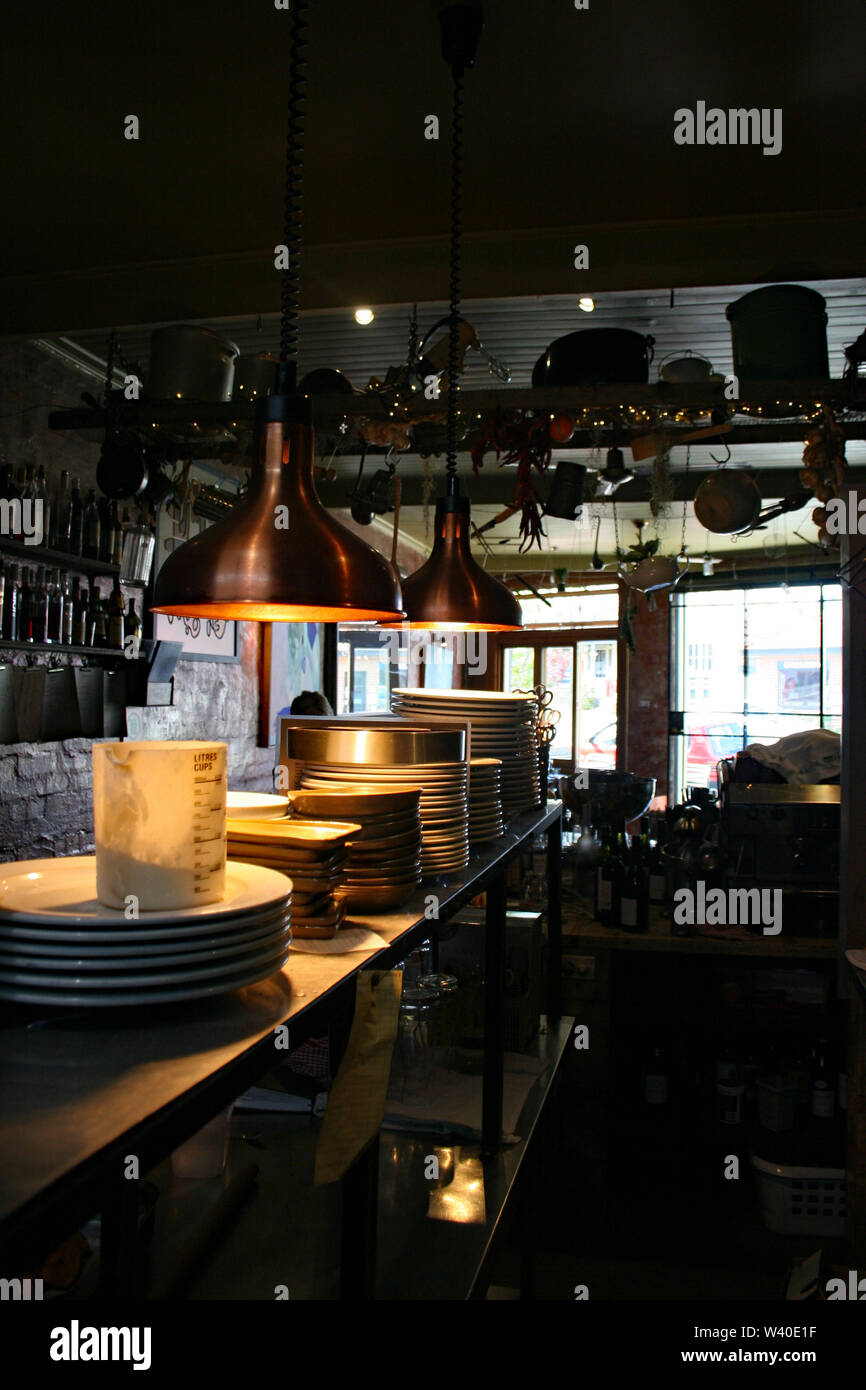 Stack Up Plates In A Small Dark Restaurant Kitchen Stock Photo Alamy