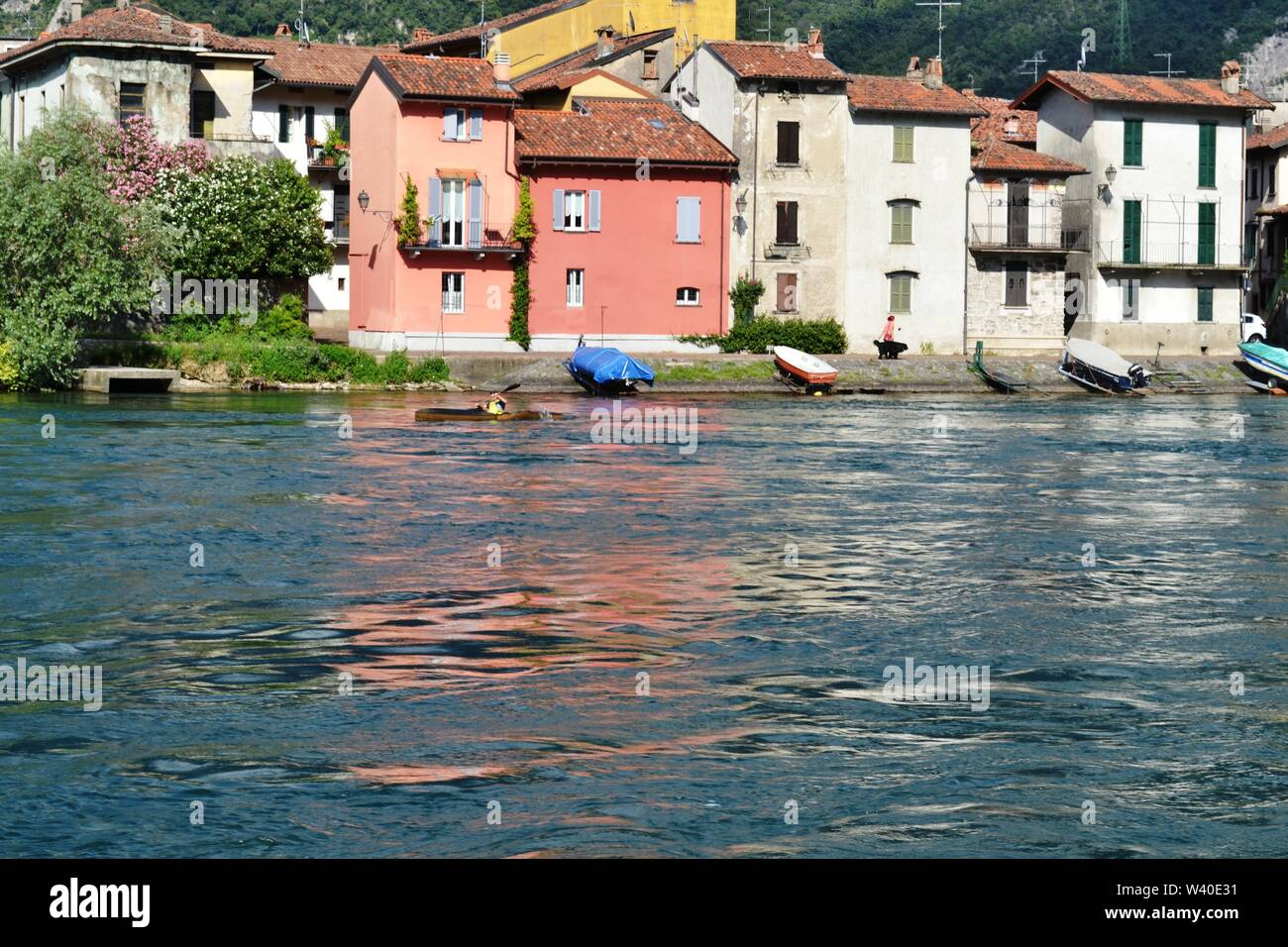 Lecco/Italy - July 10, 2014: Tourist is rowing his canoe   up the Adda river at Lecco in direction of the lake Como and Lecco in a sunny summer day. Stock Photo