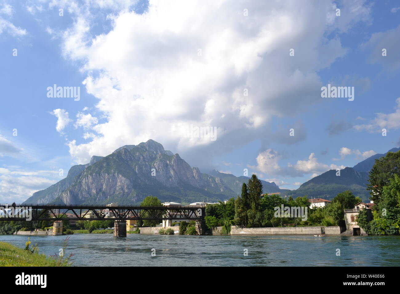Panoramic view to Lecco railway bridge and the Adda river flowing in a sunny summer day with a spectacular cloudscape over city and mountains. Stock Photo