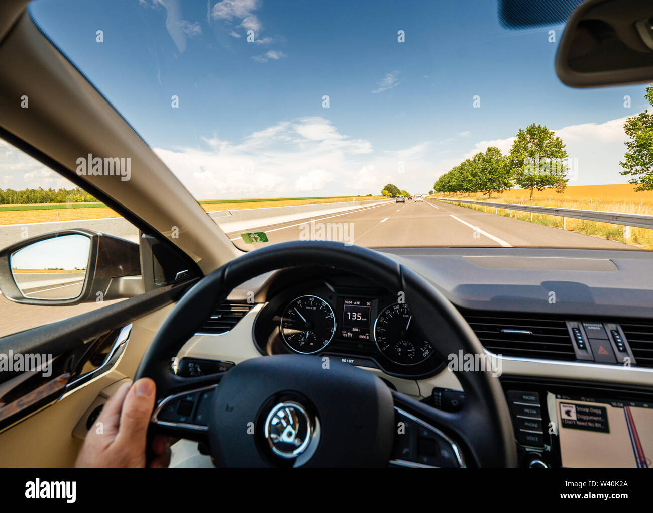 France - Jul 15, 2018: Man hand holding steering wheel driving with 135 KM per hour on French highway inside new luxury electric Skoda car - Stock Image
