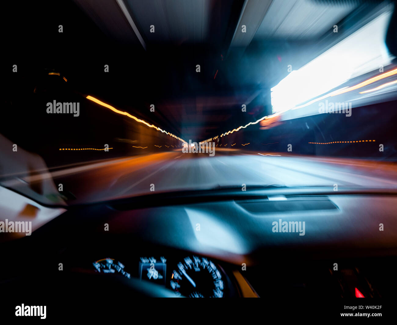 Defocused driver personal perspective point of view POV at the front commuting cars and light trails inside long tunnel safety security concept - Stock Image