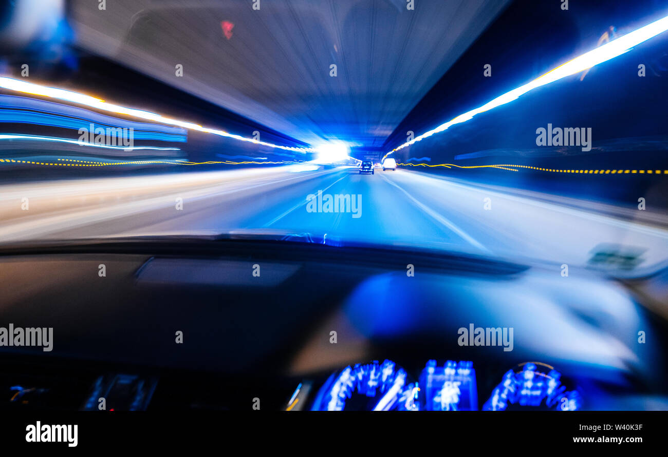 Defocused driver personal perspective point of view POV at the front commuting cars and light trails inside long tunnel safety security concept - blue color - Stock Image