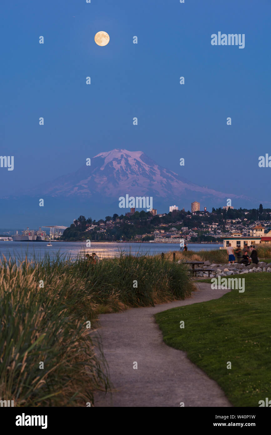 Mt Rainier Hovers Over Downtown Tacoma and Commencement Bay as Seen from Point Ruston with people walking - Stock Image
