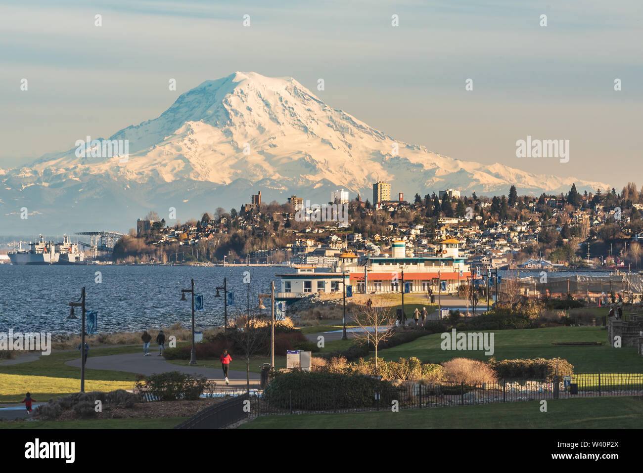 Mt Rainier Hovers Over Downtown Tacoma and Commencement Bay as Seen from Point Ruston with people walking and Riding Bikes - Stock Image