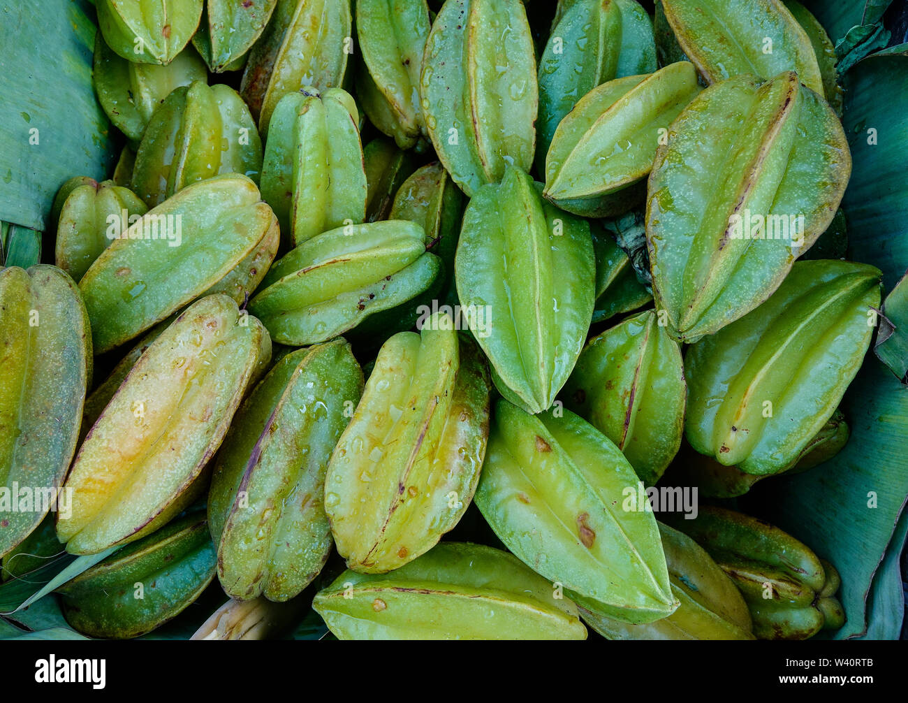 Yellow star apple fruits (Carambola) for sale at rural market. - Stock Image